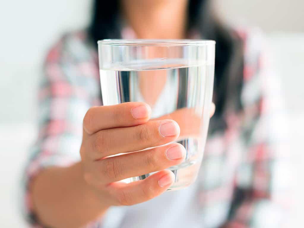 Человек держит стакан с водой
