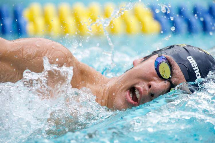 Мужчина плывет в бассейне