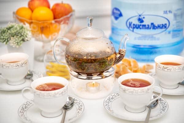 Чайник с заваркой на столе и чашки