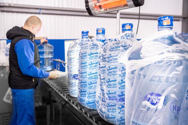 Мужчина следит за производством воды Кристальная