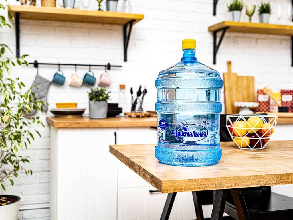Бутыль воды Кристальная стоит на столе