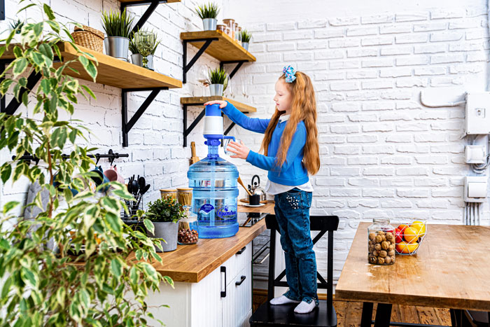 Девочка набирает воду в стакан