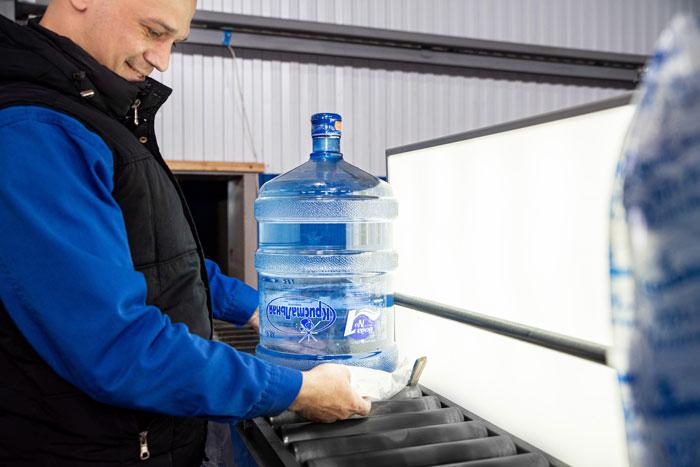 Мужчина проверяет качество воды в бутыли