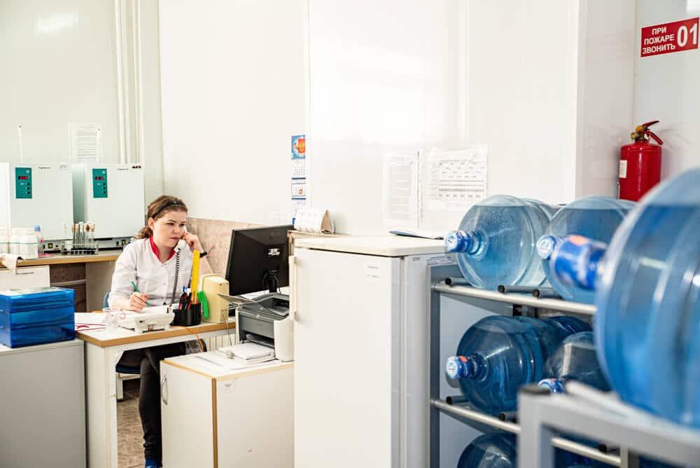 Женщина в лаборатории разговаривает по телефону