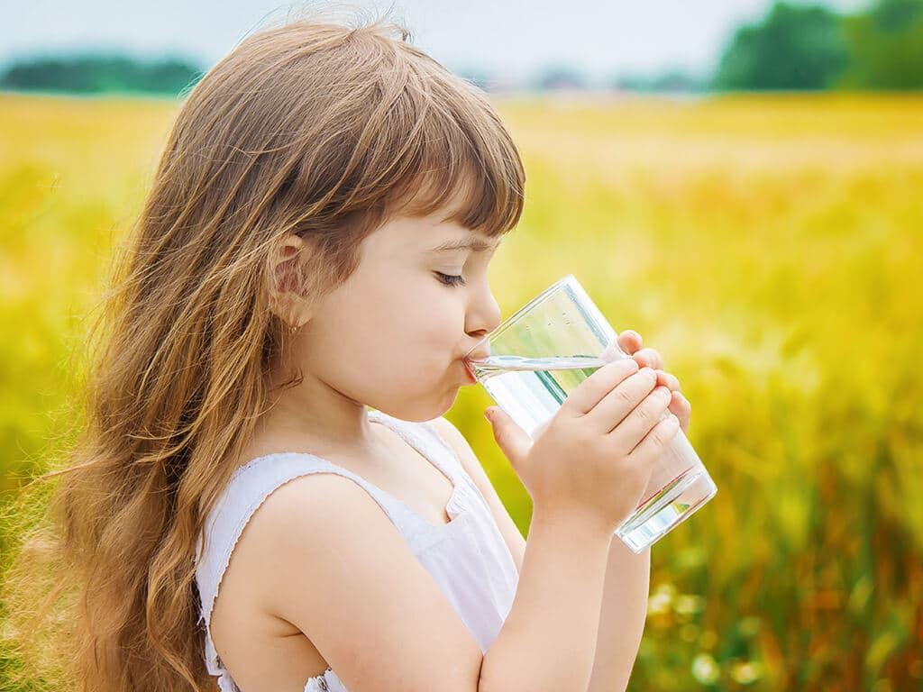 Девочка пьет воду из стакана